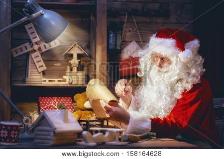 Merry Christmas and Happy Holidays! Santa Claus is preparing gifts for children for Xmas at his desk at home. Christmas legends and traditions. poster