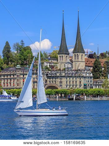 Lucerne, Switzerland - 8 May, 2016: view on Lake Lucerne from the Bahnhofquai quay - people in a sailboat, towers of the Church of St. Leodegar in the background. Lake Lucerne is a lake in central Switzerland, the fourth largest in the country.