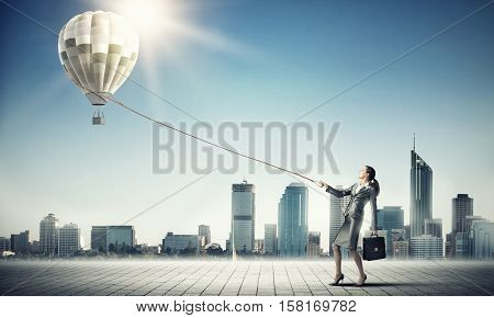 Young businesswoman pulling colorful aerostat with lead