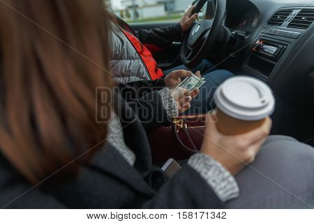 Young woman with coffee in hand coming out of taxi