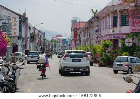 Georgetown, Penang, Malaysia - April 18, 2016 : local people and cars walking driving around the street