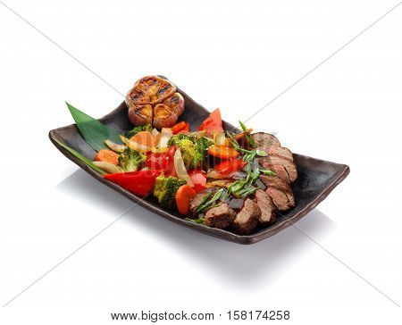 Roasted Veal With Vegetables On A Black Plate Isolated On White Background