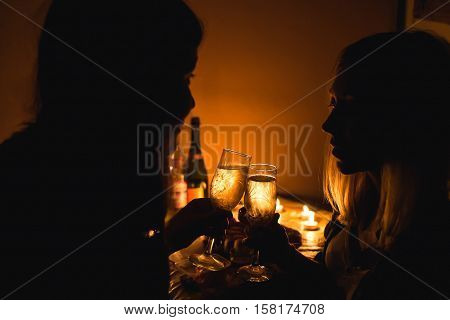 Silhouette picture of two girls clink glasses with champagne. Candle light.