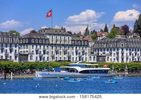 Lucerne, Switzerland - 8 May, 2016: view on Lake Lucerne from the Bahnhofquai quay - people in boats, Hotel Schweizerhof building in the background. Lake Lucerne is a lake in central Switzerland the fourth largest in the country.