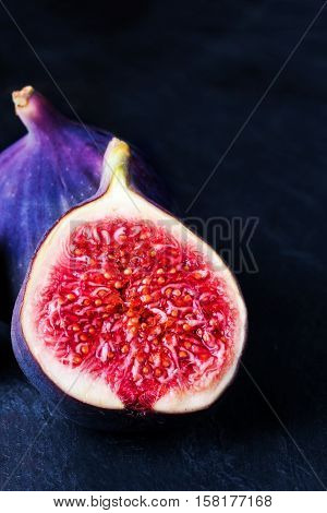 Fresh figs on black background. Beautiful blue violet figs with empty copyspace