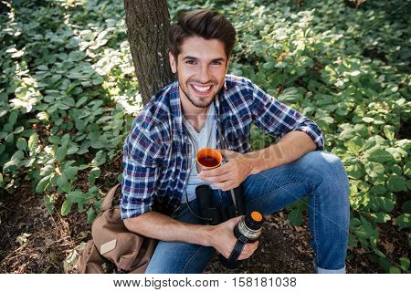 Young guy drinking tea in forest. looking at camera. top view