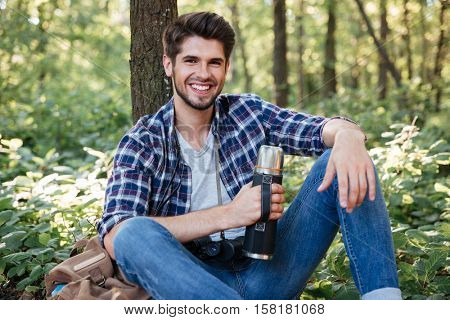 Guy sitting with thermos in forest. looking at camera