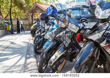 BALI / INDONESIA - NOVEMBER 23 2013: indonesain mopeds stands on parking area in bali / indonesia.