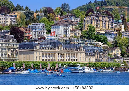 Lucerne, Switzerland - 8 May, 2016: buildings along Lake Lucerne, people in boats on the lake. Lucerne is a city in central Switzerland it is the capital of the Swiss Canton of Lucerne and the capital of the district of the same name.