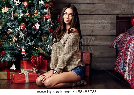 woman sittig under christmas tree with presents