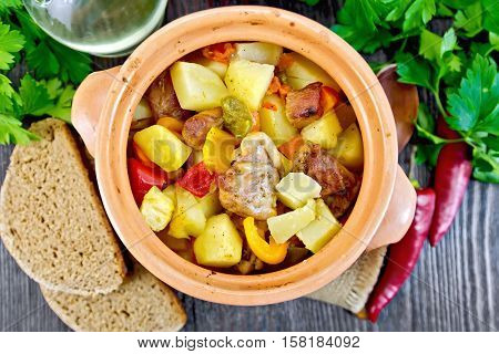 Roast with chicken, potatoes, squash and sweet peppers in a clay pot on a napkin of burlap, bread and parsley on a background of wooden boards on top