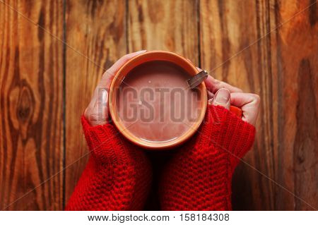 Woman holding cup of hot cacao or coffee on wooden background Closeup of hands in warm red sweaters. Top view