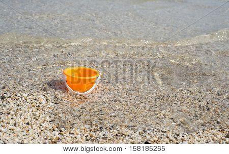 Empty orange toy bucket in the seawater