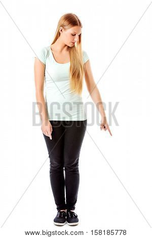 Young student woman pointing down.
