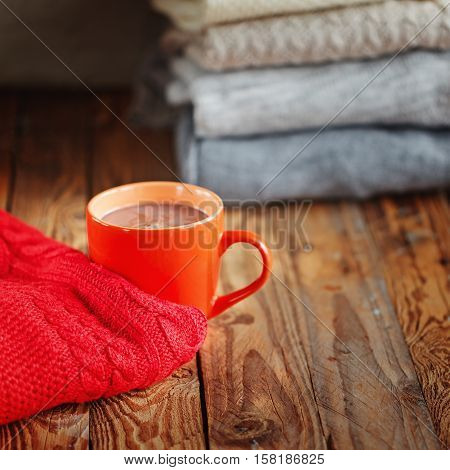 Mug with cacao or tea and red sweater on wooden table and stack sweaters background