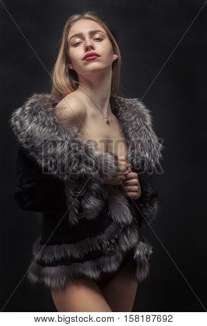 blond girl in fur coat posing on black background