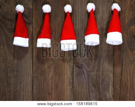 Christmas tree toys handmade. Wooden background. Making New Year decoration. Christmas ornaments. Little Santa Claus hats.