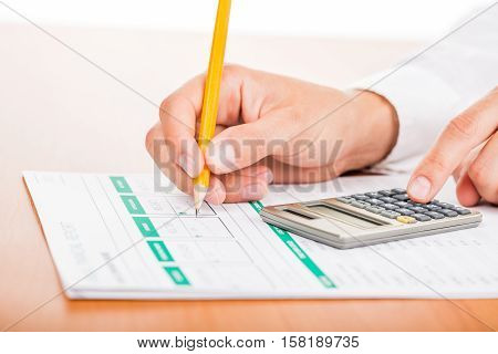 Close-up of a Businessman Using Calculator with Financial Figures