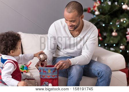 Hiding gifts. Cute adorable curly headed boy holding a Christmas tree decoration and putting it in the Christmas sock while preparing gifts
