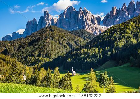 Sunny day in  Dolomites.  The valley Val di Funes - church of Santa Maddalena. Rocky peaks and forested mountains surrounded by green Alpine meadows