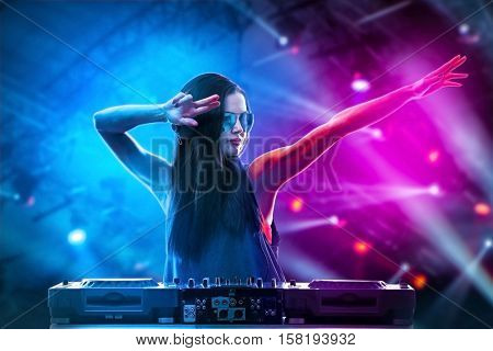 Portrait of pretty young DJ playing music on light background