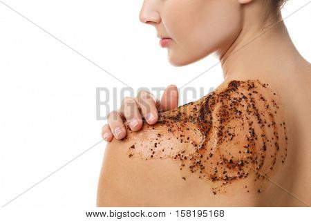 Young woman applying scrub on shoulder, closeup