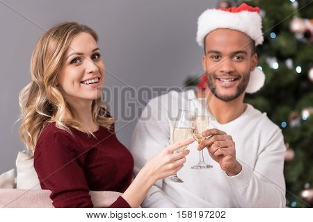 Clinking of glasses. Cheerful happy positive couple holding glasses and drinking champagne while celebrating New Years Eve
