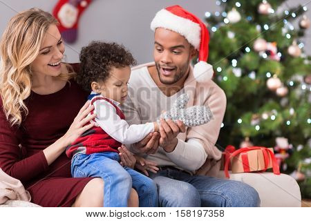 Presents for our little son. Cute nice curly headed boy trying on a mitten and focusing on the process while sitting on his mothers legs