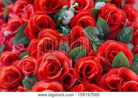 A group of red plastic roses with green leaves with a soft outer focus.