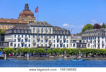 Lucerne, Switzerland - 8 May, 2016: buildings on the Schweizerhofquai quay of Lake Lucerne, people in boats and on the embankment of the lake. Lucerne is a city in central Switzerland it is the capital of the Swiss Canton of Lucerne.