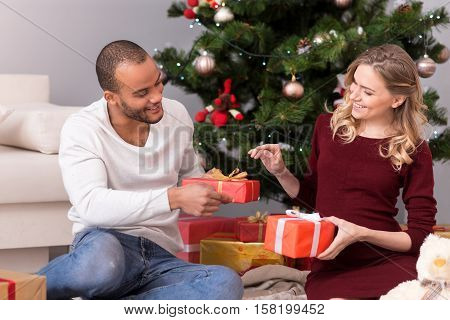 Christmas traditions. Good looking happy joyful couple sitting under a Christmas tree and looking at each other while exchanging presents