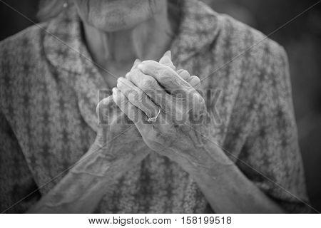 Portrait on Black Of Old woman Praying.