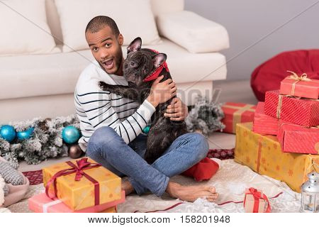 My best friend. Pleasant good looking bearded man sitting among Christmas presents and holding his dog while having a great time