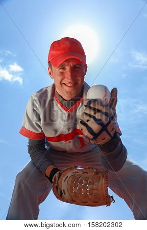 Baseball Player Bending Down and Showing Baseball Ball