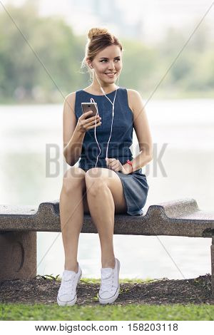 Happy woman listening music on line with headphones from a smartphone in the city park.