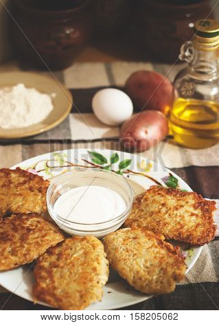 Traditional ukrainian food - deruny. Fried potato pancakes with sour cream on the check tablecloth