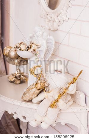 Angel Statuette With Golden Christmas Ornaments And Leaves In Bowl And Small White Santa Sitting On