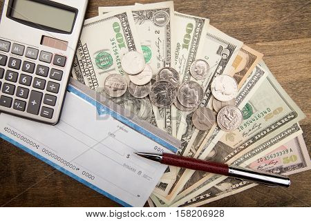 Checkbook, Pen, Calculator and Money - Close Up
