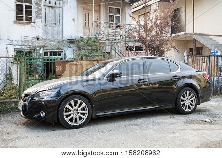 Sukhum, Russia - October 10, 2016: Lexus ES luxury sedan parked near a destroyed house where live poor people after the war with Georgia.