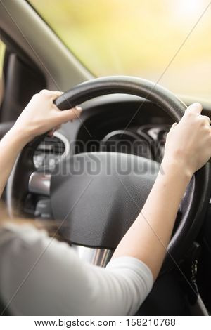 Close up of female hands on the steering. Traveler girl on car trip, looking at the road. View over shoulder. Vertical image