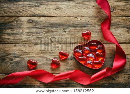 valentines day background red sweet heart in box on wooden table scarlet silk ribbon