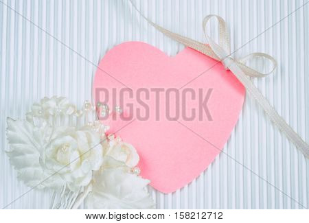 boutonniere pink heart shaped tag white silk ribbon bow on fluted paper wedding card