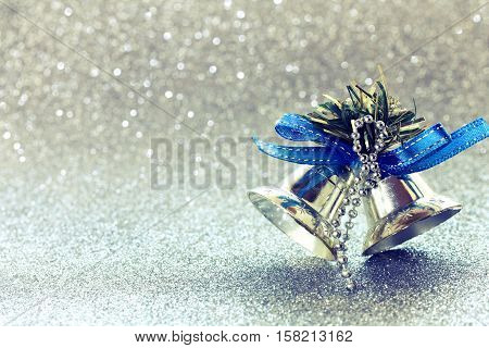 Christmas glitter blurred background silver bells baubles blue ribbon selective focus