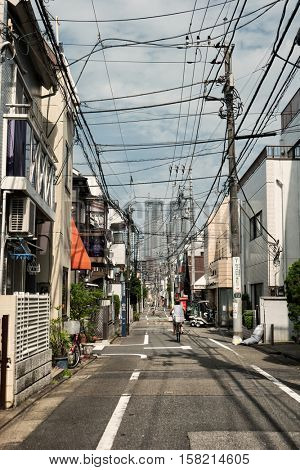 Tokyo - May 2016: Small lane with lady on bicycle, electric wires and skyscrapers in background. Nakano.
