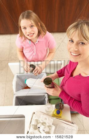 Mother And Daughter Recyling Waste At Home