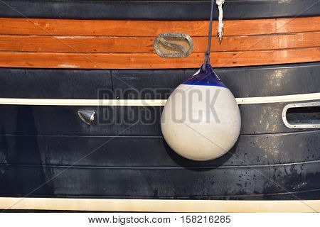 A Fender (boating) hanging on board to protect the side of the sailing vessel from the damage. Italy.