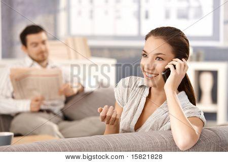 Jonge aantrekkelijke vrouw zittend op de Bank thuis, praten over mobiele, man zit in achtergrond lezing