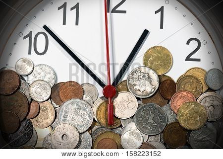 Detail a modern clock with many old vintage metallic coins. Time is money
