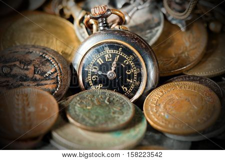 Time is money - Small pocket watch and old and vintage metallic coins