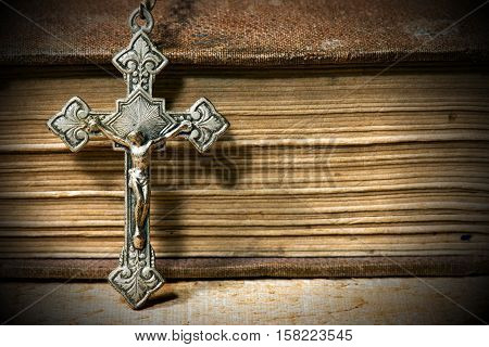 Detail of a silver small crucifix with an old Holy Bible with dark shadows on a wooden table